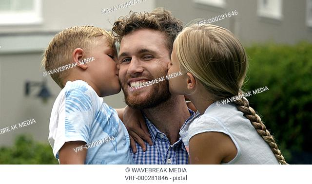 Happy children kissing their daddy