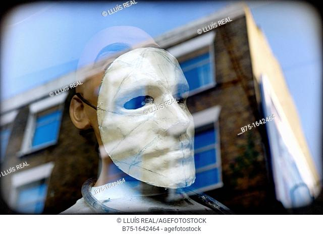 Female mannequin with a mask in shop-window glass with reflections