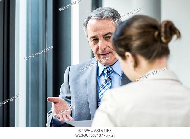 Senior businessman talking to young businesswoman