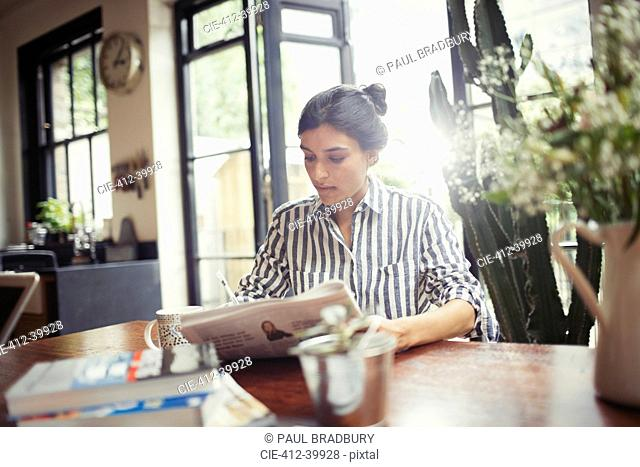 Young woman with newspaper at dining room