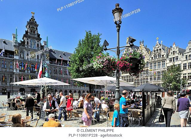 Tourists sitting on terrace of pavement café on the Grote Markt / Main Square / Grand Place with view over the City Hall, guildhalls and the st