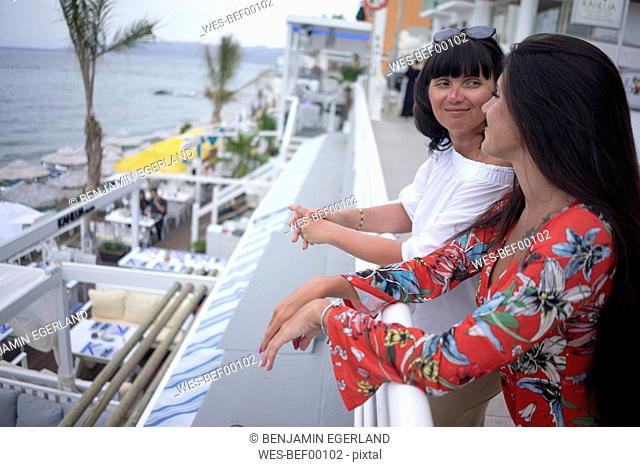 Greece, Crete, Limenas Chersonisou, mother and adult daughter relaxing on terrace