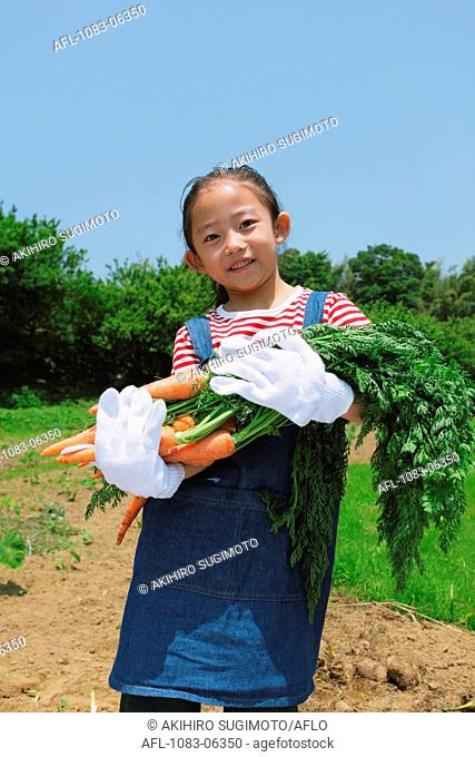 Girl Holding Bunch Of Carrot