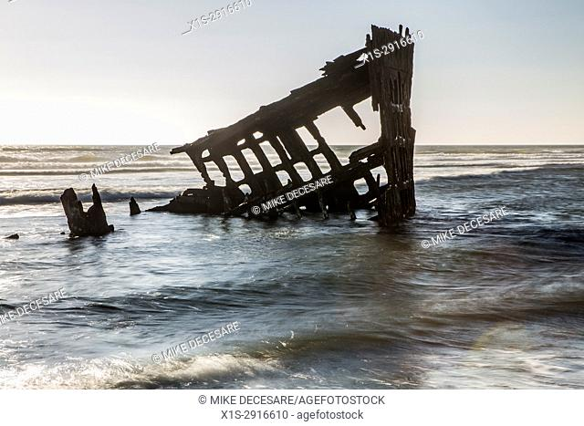 The rising tide submerges part of the Peter Iredale shipwreck that can be seen along the Oregon Coast, USA, in Fort Stevens State Park