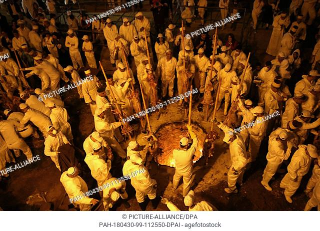 Members of the Samaritan community cook Passover Lambs inside blazing fire pits as part of the Passover Sacrifice (Korban Pesakh) ritual, at Mount Gerizim