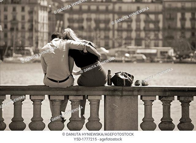 Embracing couple siting in front of Geneva Lake, Geneva, Switzerland
