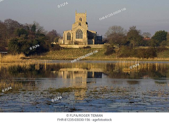 View across flooded grazing marsh towards church, St Mary's Church, Wiveton, Norfolk, England, march