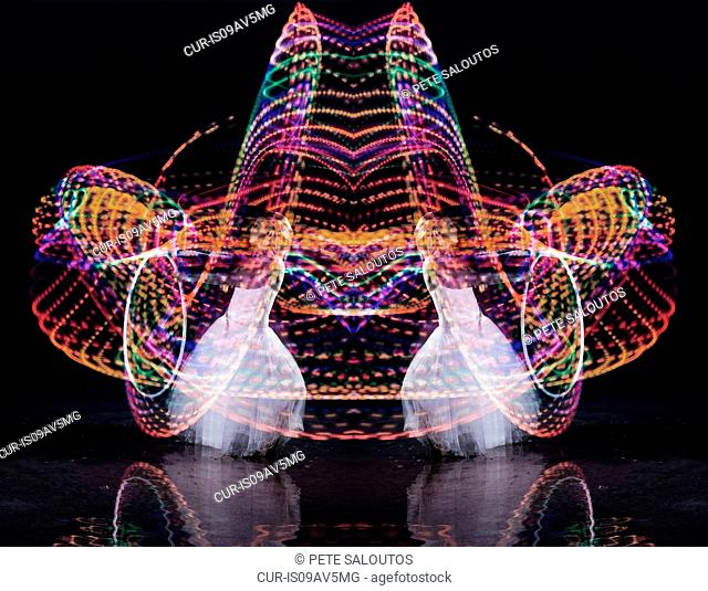 Symmetrical composite of woman dancing with illuminated hoop at night