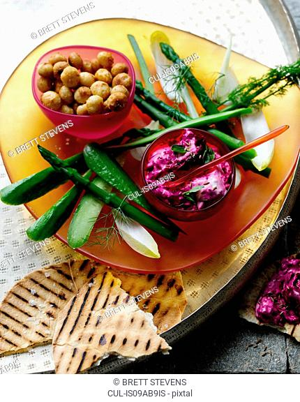 Tray with beetroot dip, macadamia nuts and grilled flatbread