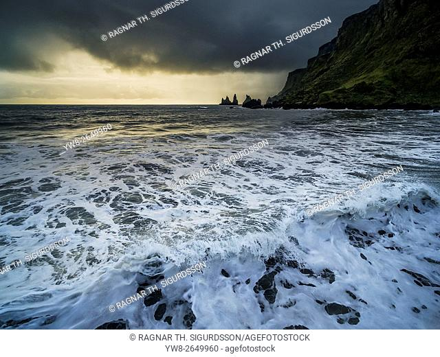 Waves crashing on the black sands at Reynisfjara beach, Reynisdrangar cliffs and Sea Stacks in the distance, Vik Myrdal, Iceland