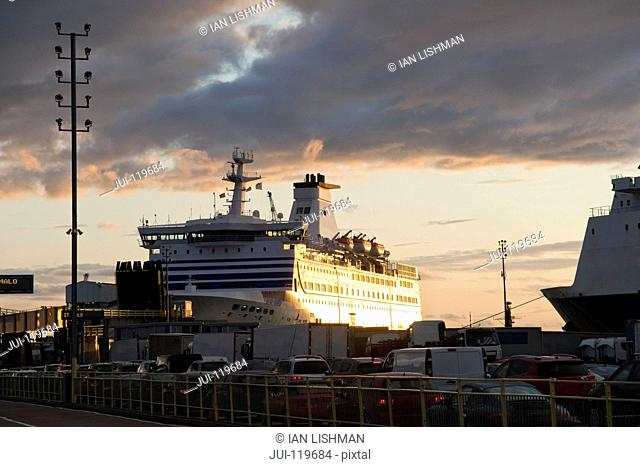 Vehicles Waiting To Board Cross Channel Ferry Docked In Portsmouth Harbour At Sunset