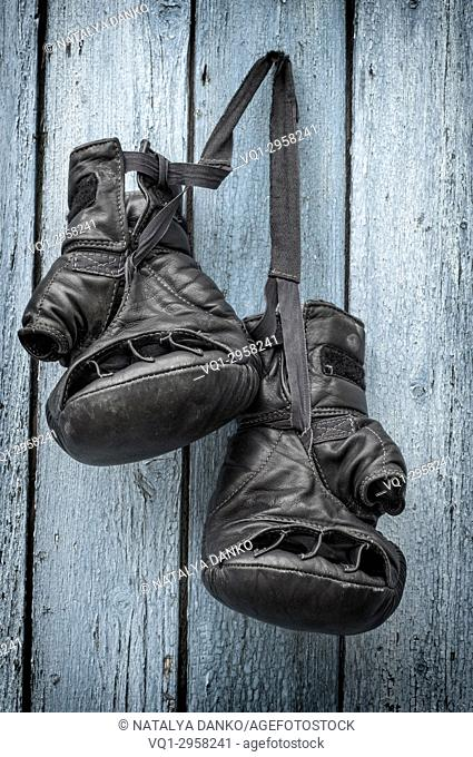 black leather gloves for kickboxing hang on a rope on a blue wooden background
