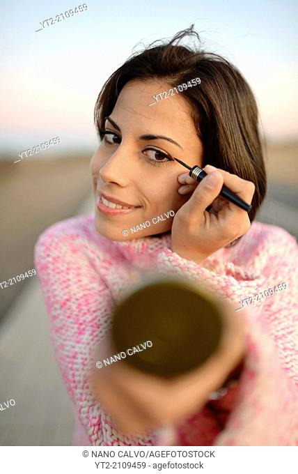 Young attractive woman applies make up outdoors