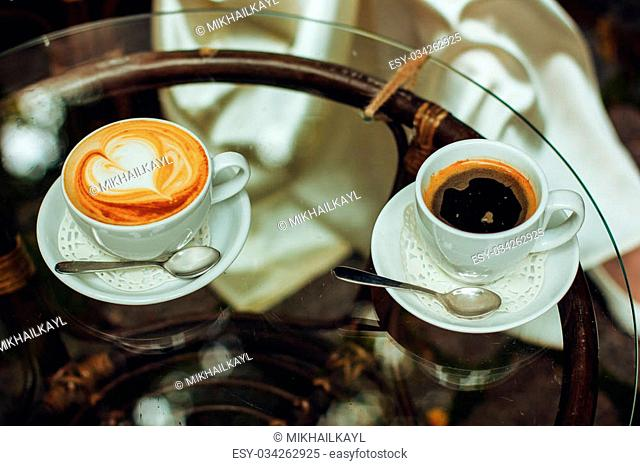 Beautiful two cups of coffee on the glass table in the restaurant