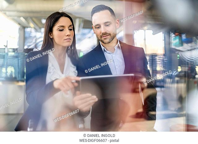 Businessman and businesswoman with tablet talking in modern factory