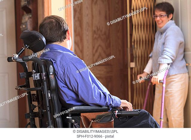 Woman with Cerebral Palsy helping man with Cerebral Palsy into home elevator