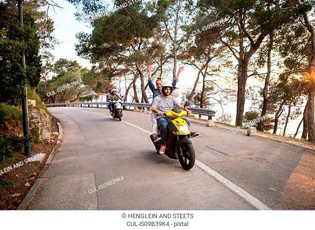 Two couples riding mopeds on rural road, Split, Dalmatia, Croatia