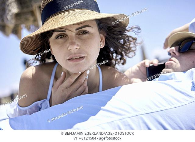 woman enjoying summer breeze, next to busy business man using phone for call, holiday, summer, vacations, couple, work-life balance
