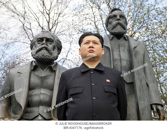 Kim Jong-un impersonator, Howard X from Hong Kong, standing in front of the Marx and Engels Statue, Marx-Engels-Forum, Berlin, Germany