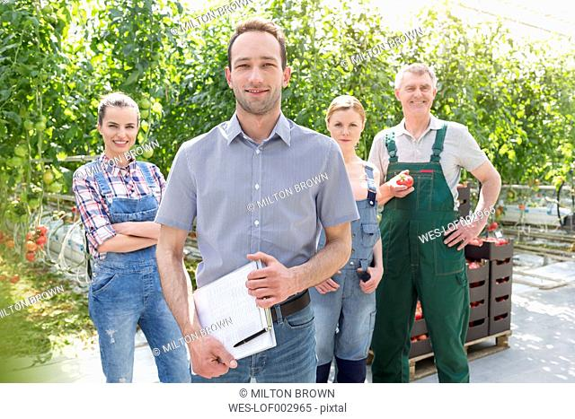 Portrait of smiling staff in greenhouse with tomatoes