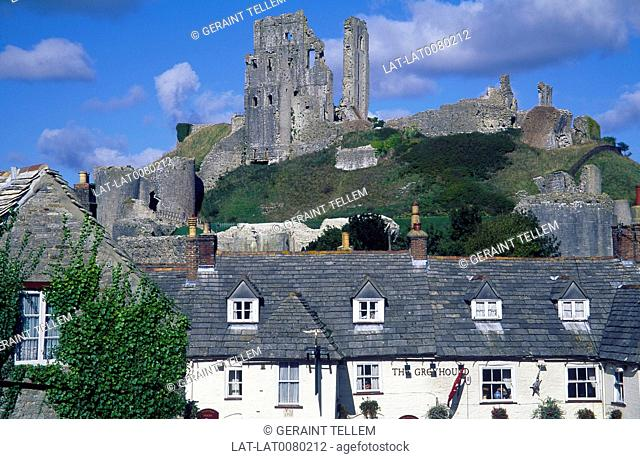 Ruins of castle on top of hill overlooking village. Houses built on perimeter wall. Greyhound Pub