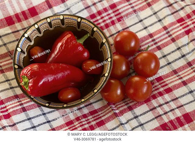 Sweet red peppers and tomatoes in brown ceramic bowl on red plaid cloth