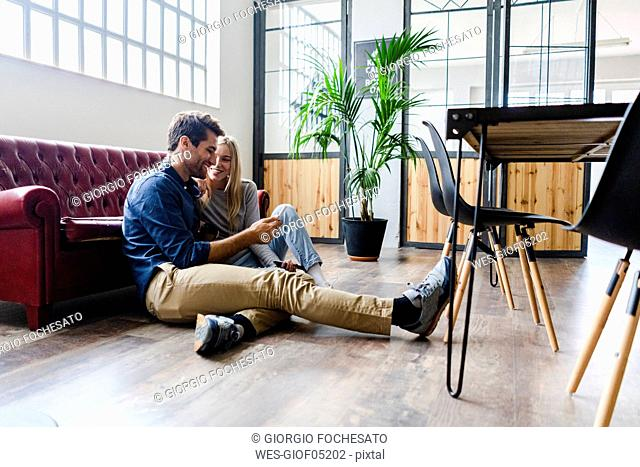 Smiling young man and young woman sitting on the floor in loft office sharing cell phone