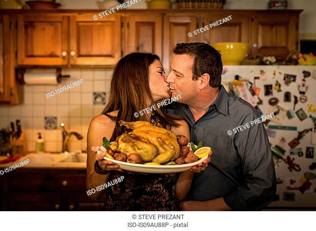 Mature couple kissing whilst holding roast chicken dinner in kitchen