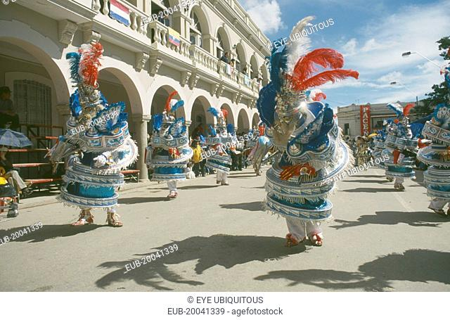 Carnival masqueraders in colourful animal costumes in a street lined with colonial buildings