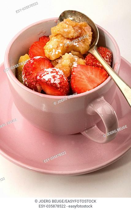 home baked kaiserschmarrn with strawberries sprinkled with powdered sugar in a cup