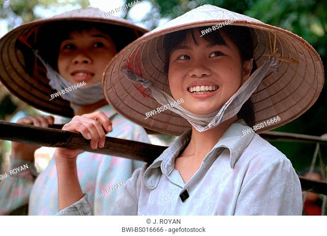 two young Vietnamese women, with the traditional vietnamese headgar, the nons, Vietnam