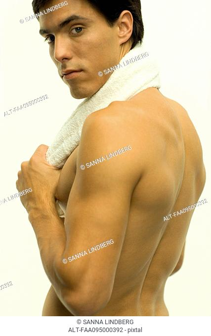 Barechested man with towel around neck, looking over shoulder at camera