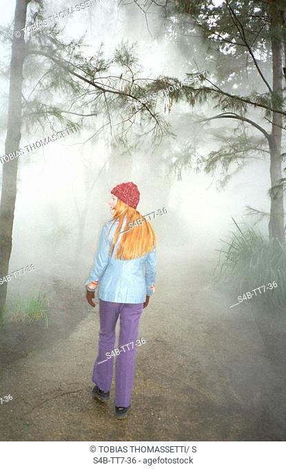 Young woman walking through foggy wood, Canberra, Australian Capital Territory, Australia
