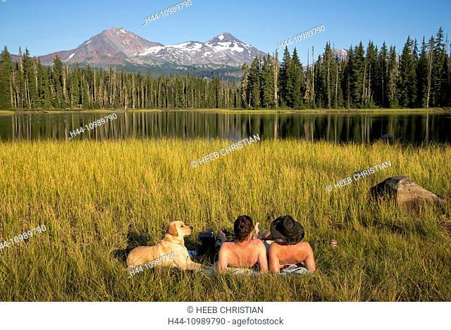 couple with dog tanning at Scott Lake, Oregon