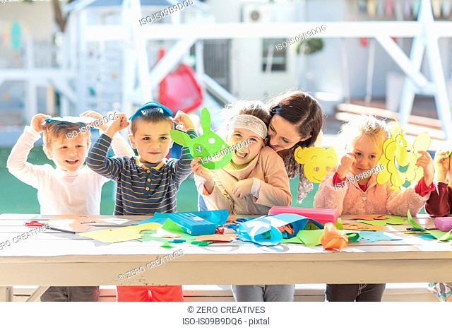 Mid adult woman helping children with crafting activity