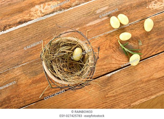 White chocolate eggs in a nest on a wooden background