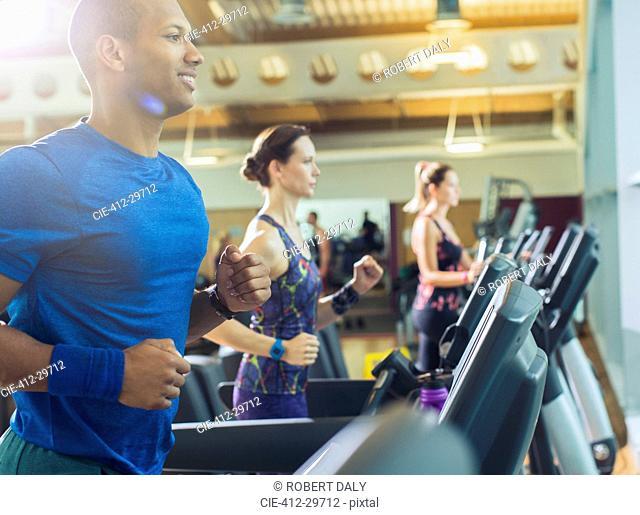 Smiling man running on treadmill at gym