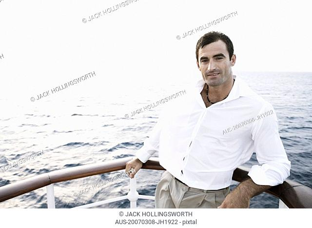 Portrait of a mid adult man leaning against the railing of a boat