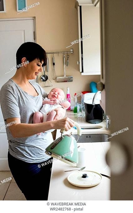 Mother holding her little baby while pouring coffee from electric kettle