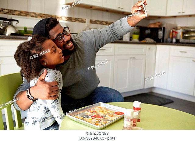 Father and daughter in kitchen, baking, father taking selfie of them both using smartphone