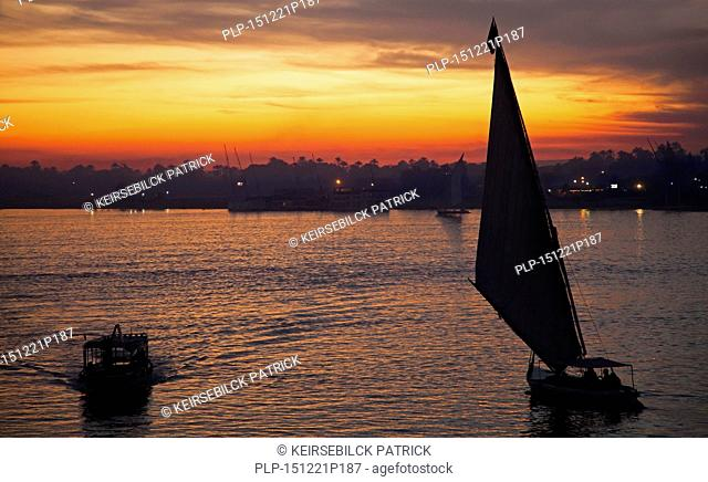 Silhouette of boats sailing on the river Nile at sunset near Luxor, Egypt
