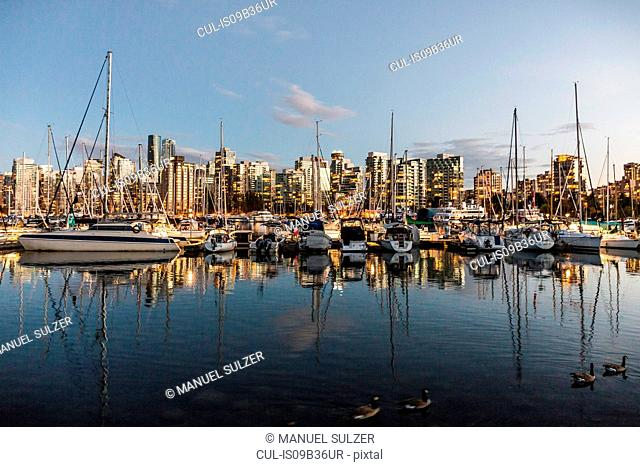 View of harbour boats and city skyline at dusk, Vancouver, Canada