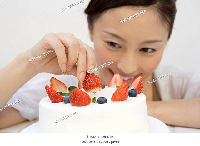 View of a young woman garnishing a pastry