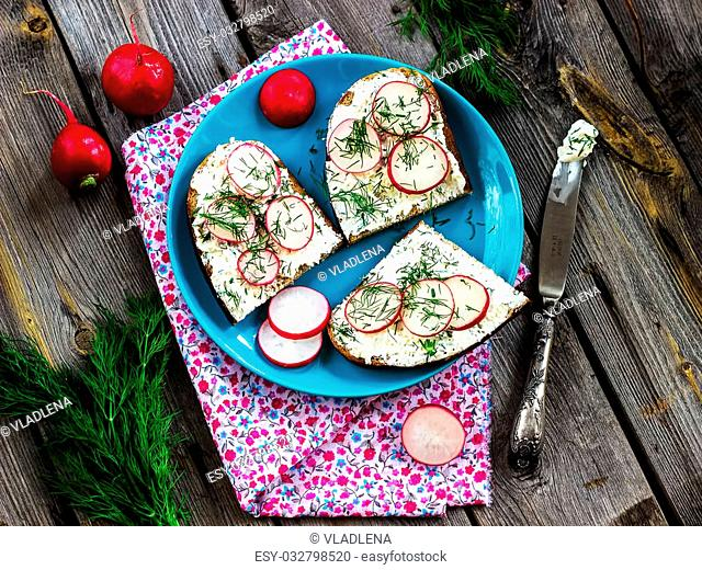 Garden radish sandwiches on a wooden table. Style rustic. Selective focus
