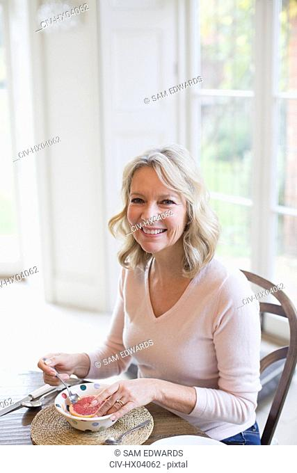 Portrait smiling mature woman eating grapefruit