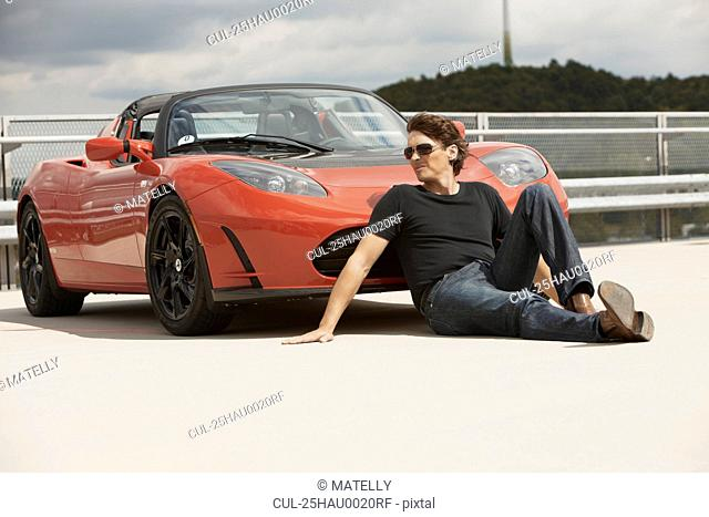 Man sitting in front of electric car