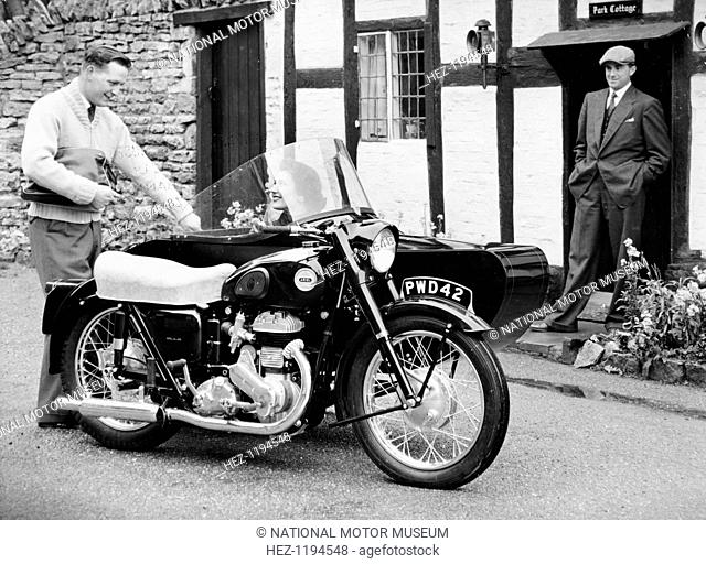 An Ariel VB 600cc with a sidecar, 1956. Parked outside a cottage, with a smiling woman sitting in the sidecar. The company was founded by James Starley and...