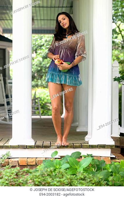 A 27 year old brunette woman wearing a short summer dress standing on a porch with a bowl of apples