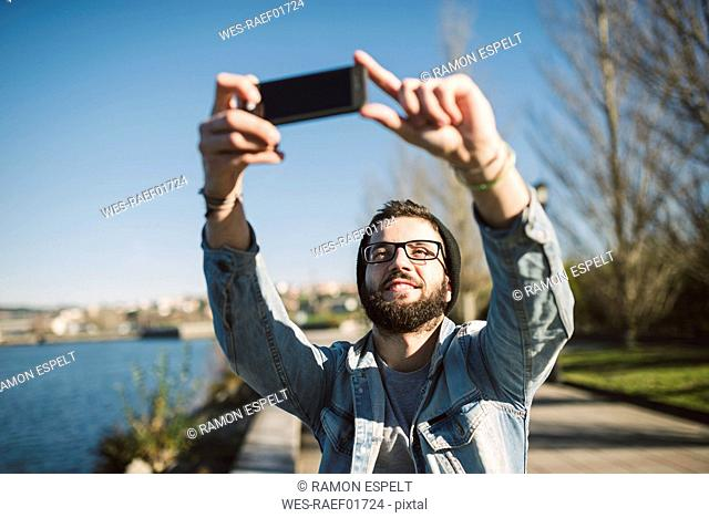 Smiling young man taking a selfie at the waterfront