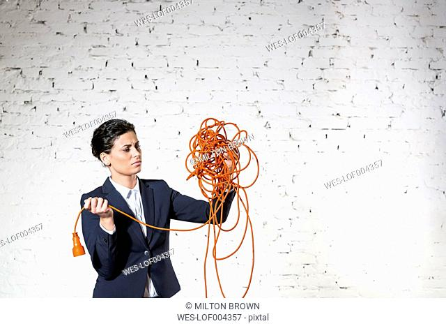 Businesswoman holding tangled extension cable